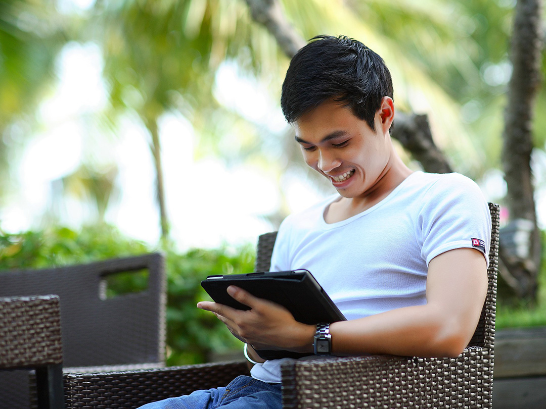 Editorial photo: Asian youth sitting at an outdoor lounge, looking at a tablet